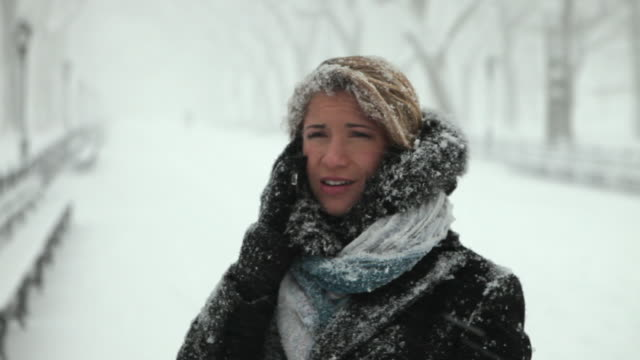 CU Young woman talking on cell phone in park in blizzard / New York City, New York, USA