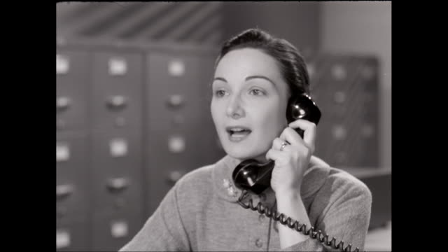 CU Young woman talking on landline phone in office / United States