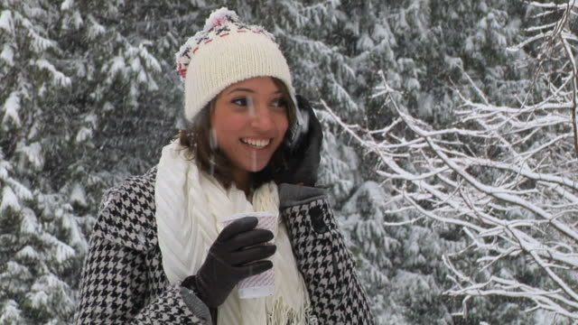 CU Young woman talking on mobile phone and drinking from disposable cup in snowy park, Vancouver, British Columbia, Canada