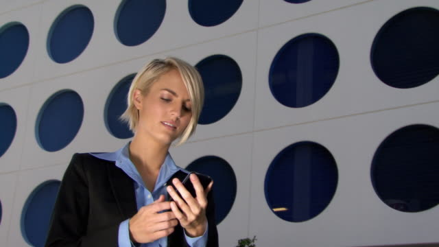MS LA Young woman talking on mobile phone in front of modern office building / Miami, Florida, USA