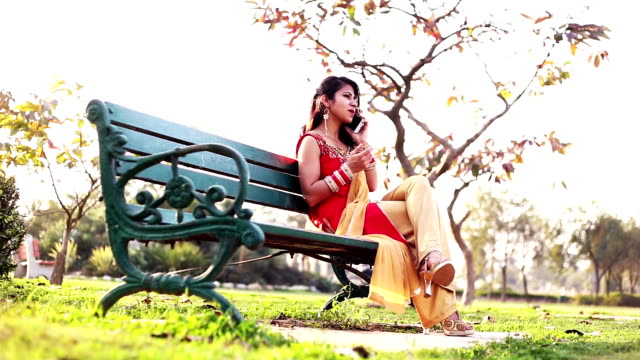 young woman talking on mobile phone - bench stock videos and b-roll footage