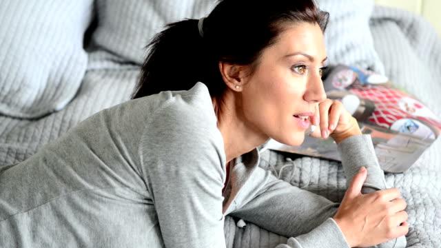 vidéos et rushes de jeune femme parlant au téléphone dans la chambre - magazine