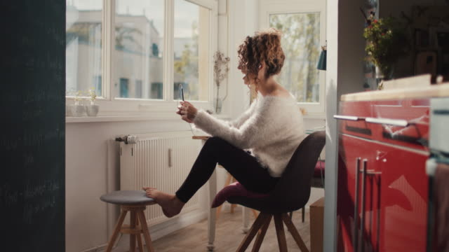 young woman talking on smartphone at home in berlin - guardare in una direzione video stock e b–roll