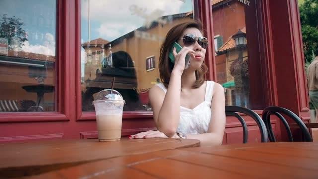 giovane donna parlando su smartphone in café - abbigliamento da neonato video stock e b–roll