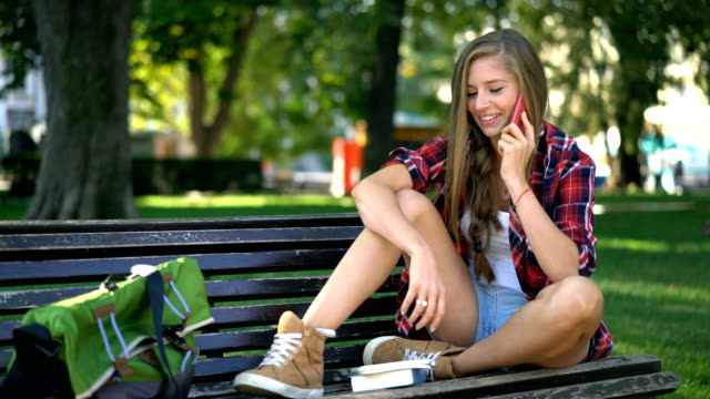 young woman talking on the phone and taking notes in her diary - 20 24 years stock videos & royalty-free footage