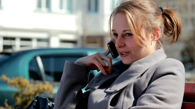 若い女性の携帯電話で話している屋外 - オーバーコート点の映像素材/bロール