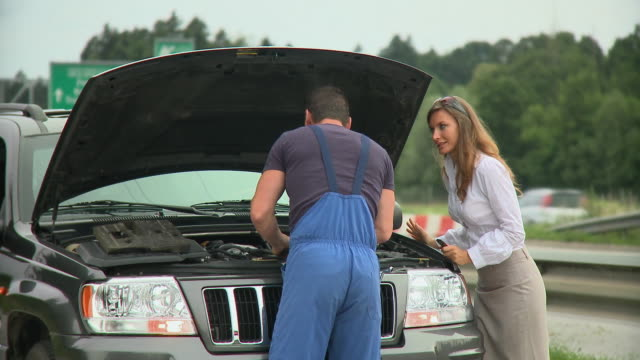 MS Young woman talking to auto mechanic repairing broken down car next to highway, Ljubljana, Slovenia