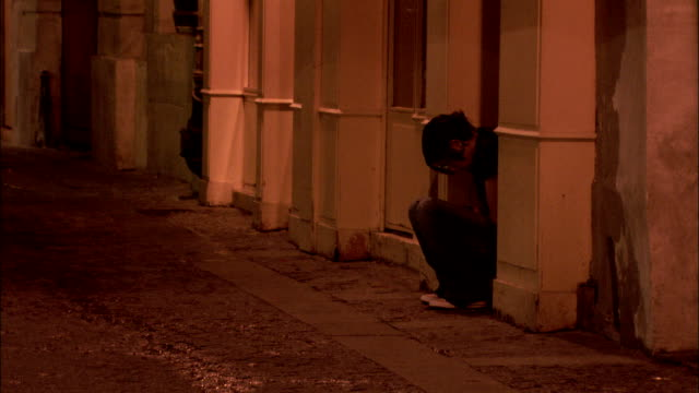 a young woman talks on a mobile phone in an alley. available in hd. - gasse stock-videos und b-roll-filmmaterial
