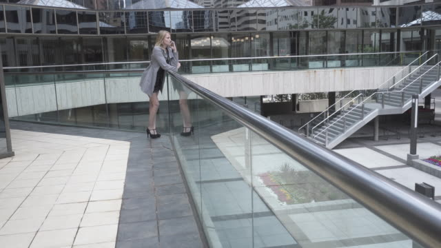 Young woman talks on phone at railing in city center