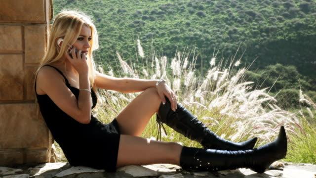 Junge Frau spricht am Telefon sitzt in der Nähe von Spalte