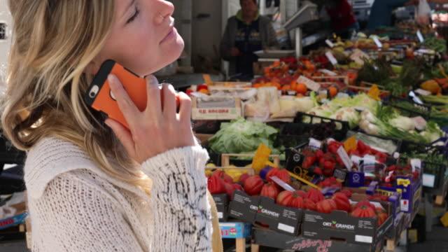 junge frau spricht über smartphone, markt hinter - marktstand stock-videos und b-roll-filmmaterial