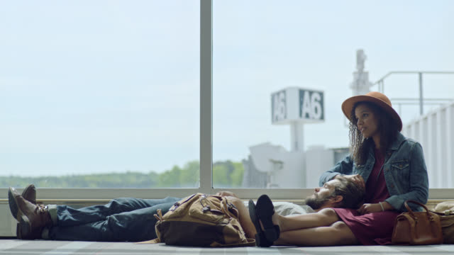 slo mo. young woman talks to boyfriend while they lounge next to gate window in airport terminal. - aspettare video stock e b–roll