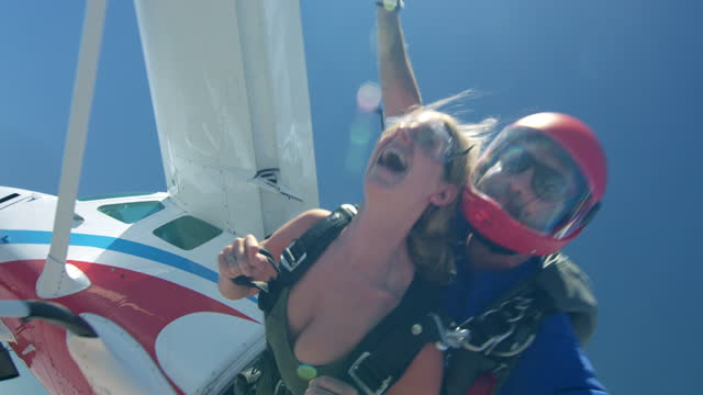 vidéos et rushes de young woman tandem skydiving from airplane - parachute