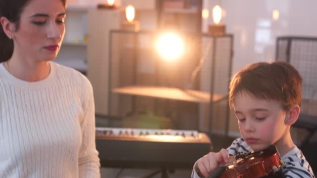 vídeos de stock, filmes e b-roll de jovem mulher ensinando um menino a tocar violino - violino