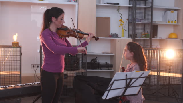 young woman teaching a little girl how to play violin - maestra video stock e b–roll
