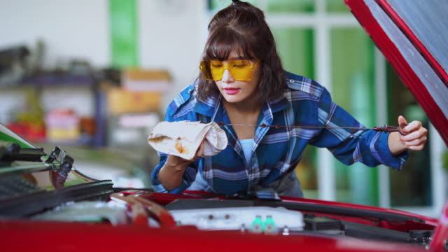 young woman technician checking engine oil in garage - wrench stock videos & royalty-free footage