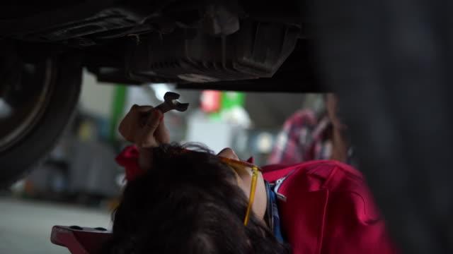 vídeos y material grabado en eventos de stock de joven técnica de la mujer examinando la parte inferior del coche, artículos de trabajo de protección roja, entrando en la parte inferior del coche - mecánico de coches