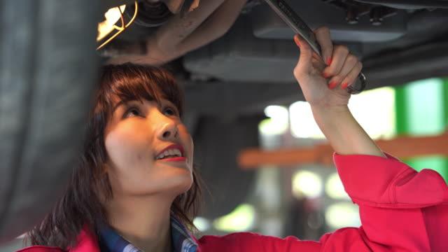 giovane tecnico donna in uniforme protettiva rossa utilizzando torcia elettrica per il controllo del motore dell'auto - solo ragazze video stock e b–roll