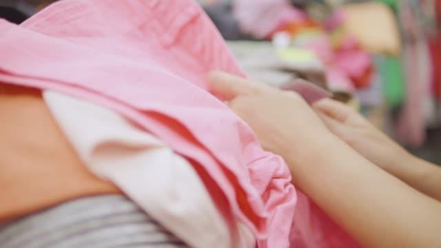 vidéos et rushes de jeune femme test et boutiques de vêtements dans un magasin de vêtements. - une seule adolescente
