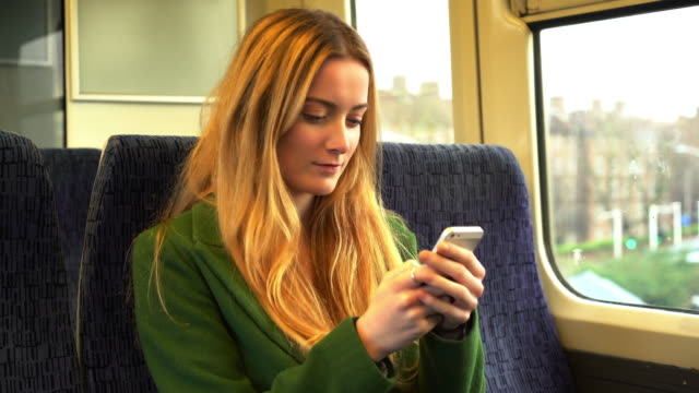 young woman text messaging on a train. - v neck stock videos & royalty-free footage