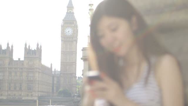 vídeos de stock, filmes e b-roll de young woman text messaging with big ben in background - sem manga