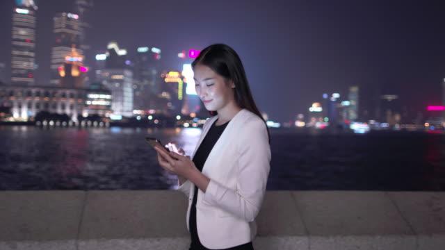 WS young woman texting at night, Shanghai, China