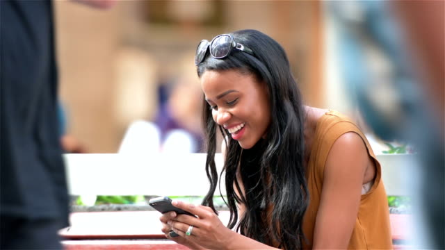Young woman texting happily