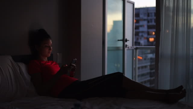 young woman texting in bed - low lighting stock videos & royalty-free footage