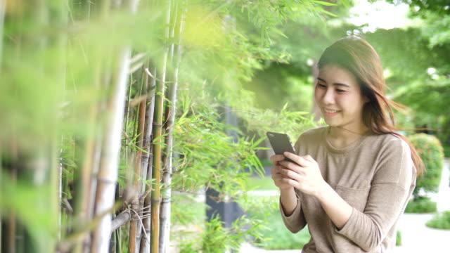 vídeos y material grabado en eventos de stock de mensajes de texto de mujer joven en el bosque - sólo mujeres jóvenes