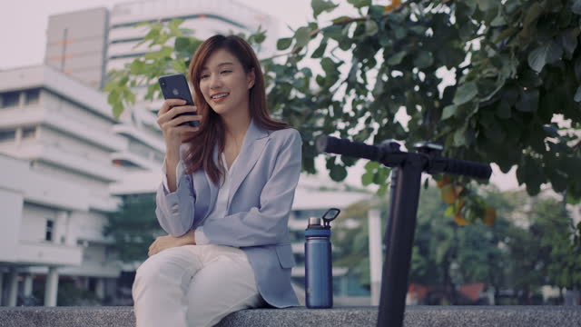 young woman texting messages on her mobile phone - sitting stock videos & royalty-free footage