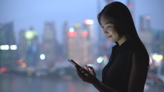 ms young woman texting on a phone by a window, shanghai, china - technophile stock videos & royalty-free footage