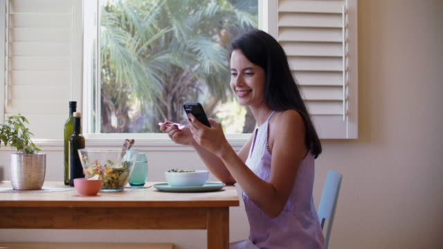 young woman texting on her phone during lunch - salad stock videos & royalty-free footage