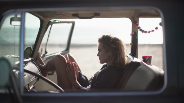 stockvideo's en b-roll-footage met ms young woman texting on her phone in her camper van - vorm van communicatie