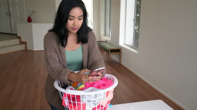 ms young woman texting on her phone while doing housework - housework stock videos & royalty-free footage