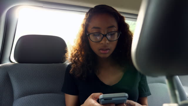 MS R/F Young woman texting on smartphone in backseat of car while in discussion with other passengers