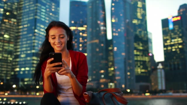 vídeos y material grabado en eventos de stock de ms young woman texting on the phone in the city at night. - hacer un descanso