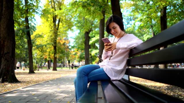 若い女性のテキストメッセージ - ベンチ点の映像素材/bロール