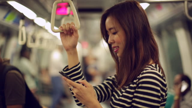 ms young woman texting while travelling on train. - republik singapur stock-videos und b-roll-filmmaterial
