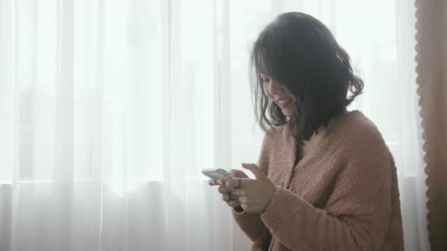 年輕女子用智慧手機發短信,在酒店房間微笑。 - 回答 個影片檔及 b 捲影像