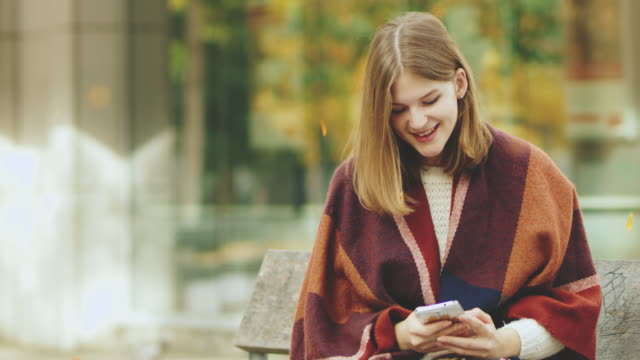 ms young woman texting with smart phone in autumn park - warm clothing stock videos & royalty-free footage