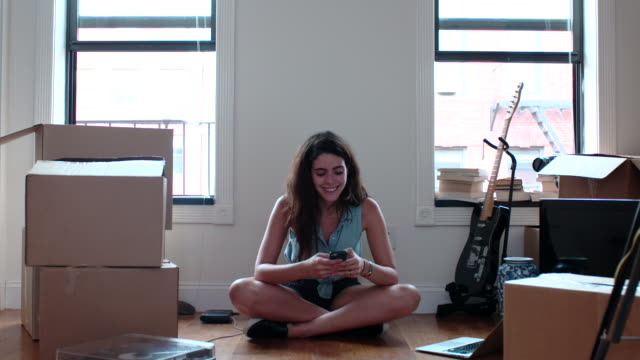 vídeos de stock, filmes e b-roll de young woman texts cell phone in her new apartment - sentar