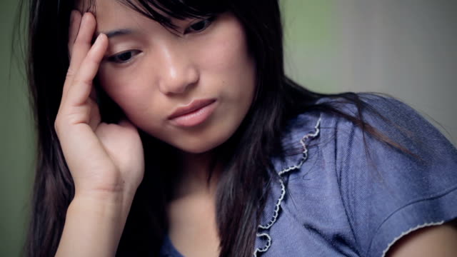 vidéos et rushes de jeune femme pense profondément. - se tenir la tête entre les mains