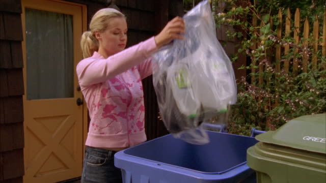 MS, Young woman throwing garbage into recycling bin in front of house, Cambria, California, USA