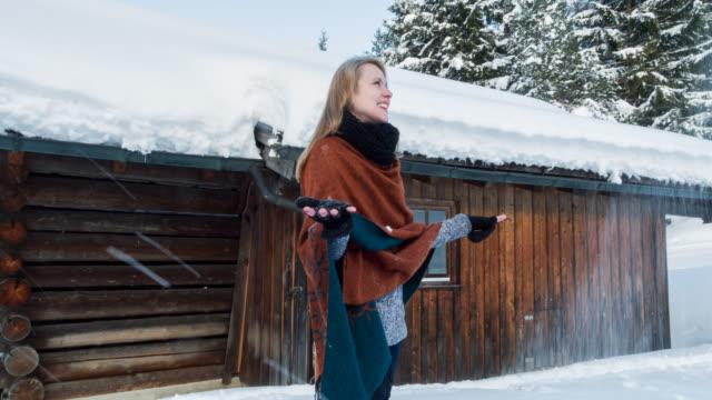 vidéos et rushes de young woman throwing snow at a log cabin in winter - châle