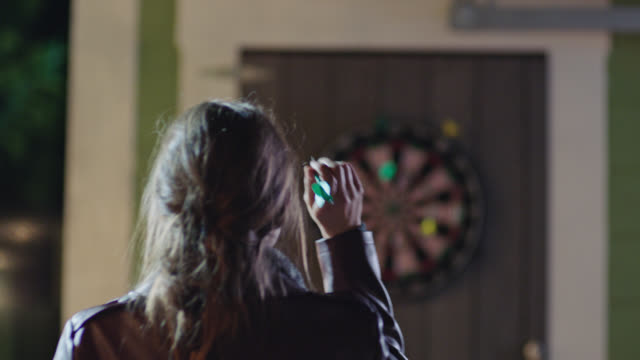 Young woman throws dart at dart board and curtseys to her partner.