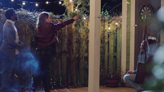 young woman throws darts with friends on back patio at house party. - ダーツバー点の映像素材/bロール