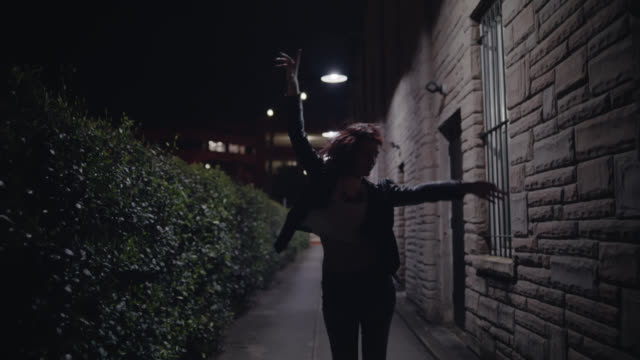 WS SLO MO. Young woman throws hands in air dancing in stone alley at night.