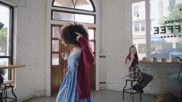 SLO MO. Young woman throws her hands up and dances around coffee shop as people watch and snap smartphone photos.
