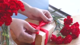Young woman tie a bow for packaging handmade beautiful gift box for mothers day gift at home with red carnations bouquet isolated on wooden table, close up closeup concept