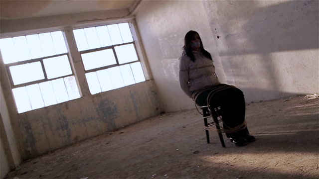 Young woman tied to a chair in a empty room